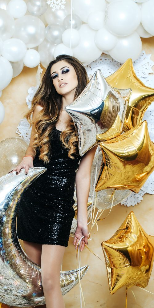 sexy christmas pretty sexy woman or cute girl in black glowing dress near silver moon and golden stars on white balloons and decorative new year snowflakes background